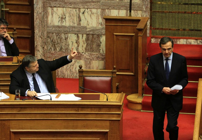 Leader of conservative New Democracy party Samaras leaves a podium as Finance Minister Venizelos raises his hand during a parliament session in Athens